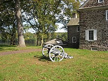 Photo shows an 18th century cannon, probably a 3-pounder, with an old stone building and the Delaware River in the background.