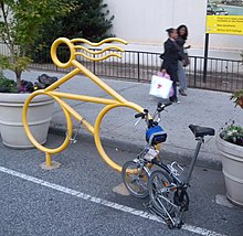 A bike rack shaped like a stylized bicycle with a rider with hair streaming in the wind. It is painted yellow and set in tarmac at the edge of a road between two large concrete plant pots. A folded bicycle is parked there and an abandoned chain hangs from it. Behind, two women walk past on the sidewalk in front of black iron railings.