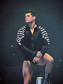 A caucasian male with black hair stands on the turnbuckles of a wrestling ring, with on foot on the top rope and the other on the middle rope, while looking to his right. He is wearing short black wrestling tights and black and silver wrestling boots, with a black jacket featuring a silver design on both sleeves.