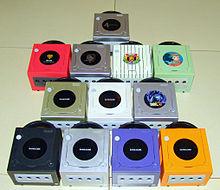 Nintendo GameCube in diverse colorazioni. In prima fila sono visibili, da sinistra a destra, i modelli denominati Jet, Platinum, Indigo e Spice