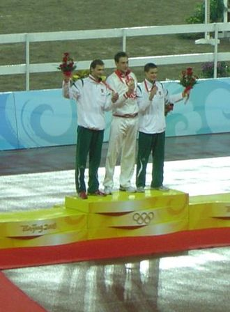 Andrey Moiseyev - Moiseyev (centre) on the podium with his gold medal from the 2008 Olympics.