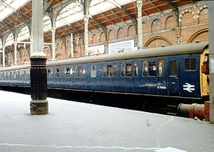 British Rail Class 307 - British Railways Class 307 train in plain blue livery on a working to Southend Victoria awaits its correct departure time at London Liverpool Street station. The frosted windows show the location of the toilets. The second carriage includes some first-class seating.