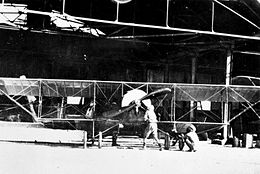 Front view of single-engined biplane and two men in front of a large open hangar