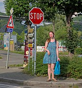 A person in blue standing next to a stop sign in Anseremme, Belgium (DSCF7416).jpg