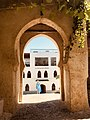 A view on gate and a man in traditionnal moroccan clothing In tangiers Morocco.jpg