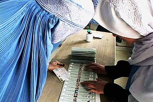 Afghan presidential election, 2004 - A Joint Electoral Management Body employee, right, explains how to fill out an election ballot to an Afghan woman in the village of Raban
