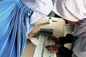 2004 Afghan presidential election - A Joint Electoral Management Body employee, right, explains how to fill out an election ballot to an Afghan woman in the village of Raban