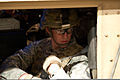Air Force Senior Airman Daniel Meness, a civil affairs specialist with Provincial Reconstruction Team Kapisa, buckles himself into a simulated armored vehicle used to train Soldiers to respond to improvised 111216-A-PX072-143.jpg