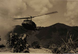 """A Sầu Valley - An undated photo of a Bell UH-1 """"Huey"""" helicopter landing with soldiers of the 101st Airborne Delta Raiders in the A Shau valley near Hue, Vietnam."""