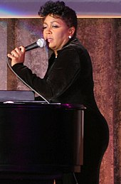 A woman sings while she is recharged on a piano. She wears a long black ensemble and diamond earrings.