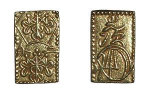 Zwei rechteckige Goldmünzen aufrecht stehend nebeneinander, auf beiden sind verschlungene Ornamente abgebildet