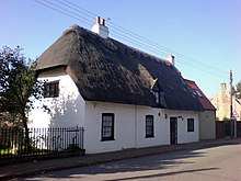White thatched cottage single storey 3 windows 1 front door 1 attic window chimney No front garden