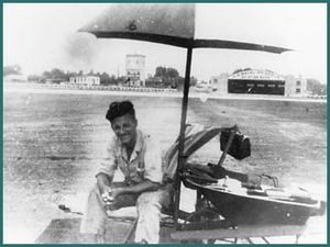 Archie League - Archie League is shown while on duty during the summer at Lambert-St. Louis International Airport. His equipment included rolled-up flags in the wheelbarrow, the dangling lunch box, a folding chair, drinking water, and a pad for taking notes.