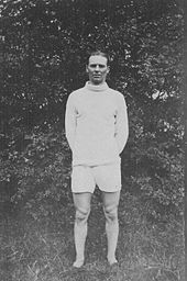 A man with dark hair is wearing a white top and white shorts. He is standing on a grass field.