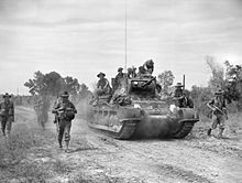 Soldiers advance along a road beside a tank
