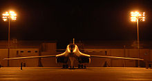 Front view of B-1 parked on ramp at night. Nearby yellow flood lights illuminate the area. In the background are buildings