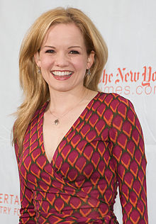 A smiling blonde woman wearing a red wrap dress, standing in front a wall with text on it