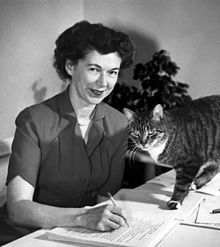 Cleary at her desk writing, joined in the photo by her cat.