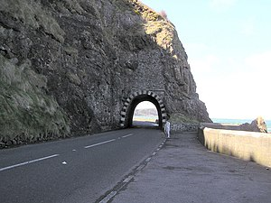 "A2 road (Northern Ireland) - The Blackcave Tunnel or ""Black Arch"" at the start of the Antrim Coast Road at the northern edge of Larne."