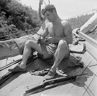 Special Boat Service - Corporal Aubrey sharpens his fighting knife as he prepares for combat in the Aegean Sea in 1944