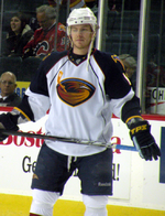 A Caucasian hockey player. He wears a white jersey with dark blue shoulders with a stylized brown thrasher holding a hockey stick for a logo. He holds his stick parallel to his waist.