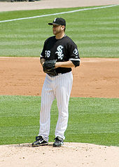 A man standing on a pitcher's mound holds a baseball in his black baseball glove. He is wearing a black-and-white baseball uniform.