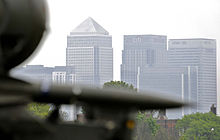 Photograph of a missile system in the foreground and the Canary Wharf skyline in the background.
