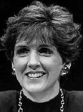 A black and white image of a pale-skinned woman in her early forties, with fairly dark hair with a swept hairdo covering part of her ears, smiling, wearing solid metal earrings and a metal chain necklace and a dark top.