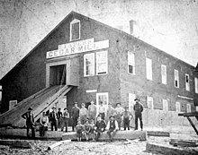 "A black and white photograph of a large building featuring a sign that reads ""E Faber's Cedar Mill""; More than a dozen white men sit on a large cedar log in the foreground"