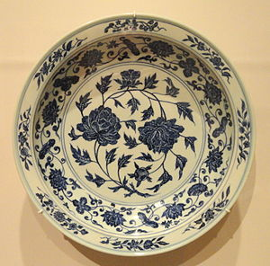Cavetto - Ming dynasty dish in blue and white porcelain. The cavetto is demarcated by pairs of thin blue lines, and has running scroll decoration, different to that on either side of it in the flat middle and rim.