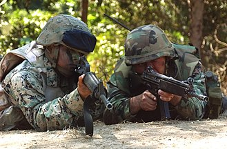 Heckler & Koch HK33 - A Chilean Marine (right) aiming the HK33A2 during training alongside U.S. Marines.