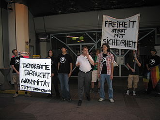 """Democratization of technology - At a demonstration at BMVIT, banners read, """"Democracy needs anonymity - stop data retention"""" (left) and """"Liberty dies with security"""" (right)."""