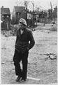 Depression-Unemployed, man dressed poorly walking with head down, shacks in background, no credit Typical picture... - NARA - 195916.tif