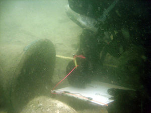 Ship's bell - An underwater archaeologist with the Lighthouse Archaeological Maritime Program in St. Augustine, Florida, recording the ship's bell discovered on the 18th century Storm Wreck.