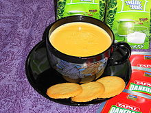 A cup of tea with cookies on the saucer
