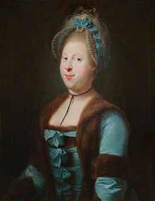 Left-looking portrait of a woman wearing a blue dress, trimmed with fur