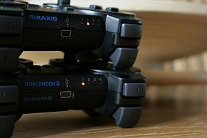 DualShock - Comparison of the tops of DualShock 3 and Sixaxis controllers, showing DUALSHOCK 3 and SIXAXIS labels, USB Mini-B port, controller number LEDs and analog L1/L2 triggers.