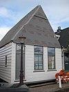 foto van Houten huis met houtskelet. Puntvormig voorschot