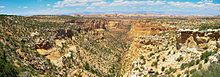 Panorama of a desert landscape with a canyon running through the center of the picture.