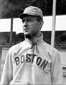 "A man wearing a baseball cap and jersey with ""Boston"" written across the chest shown from the waist up looks to the left."
