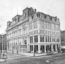 Photograph of the exterior of Booth's Theatre, viewed from diagonally across the intersection of 23rd Street and Sixth Avenue.