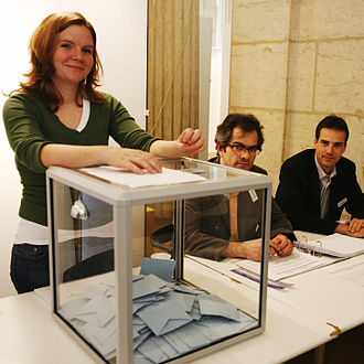 Elections in France - Scene inside a polling station during the French presidential election of 2007: election officials and a standard transparent ballot box.