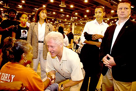 Clinton greets a Hurricane Katrina evacuee, September 5, 2005. In the background, second from the right, is then-Senator Barack Obama. FEMA - 14697 - Photograph by Ed Edahl taken on 09-05-2005 in Texas.jpg