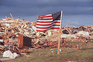 1999 Bridge Creek–Moore tornado - An American flag blows in the wind next to the remains of a home destroyed by the tornado.
