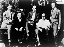 Five well-dressed men seated or standing at various levels