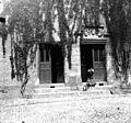 Femme chapautée assise sur le perron dune maison de maître (6966032866).jpg