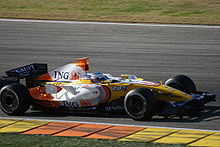 a brightly coloured F1 car drives on a track