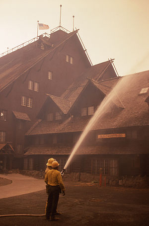 Old Faithful Inn - A firefighter sprays water on the roof as a precaution during the 1988 fires