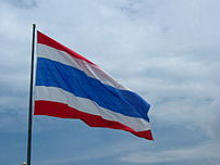 A flag of Thailand on the top of a pole.