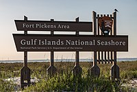 "Wooden sign saying ""Fort Pickens Area, Gulf Islands National Seashore"" standing in front of a beach at sunset"